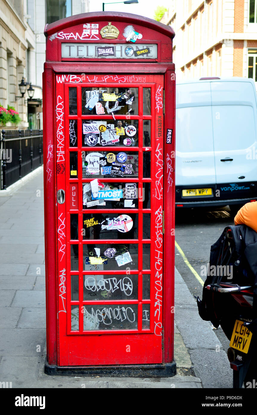 Traditional red telephone box covered in graffiti and stickers, central London, England, UK. - Stock Image