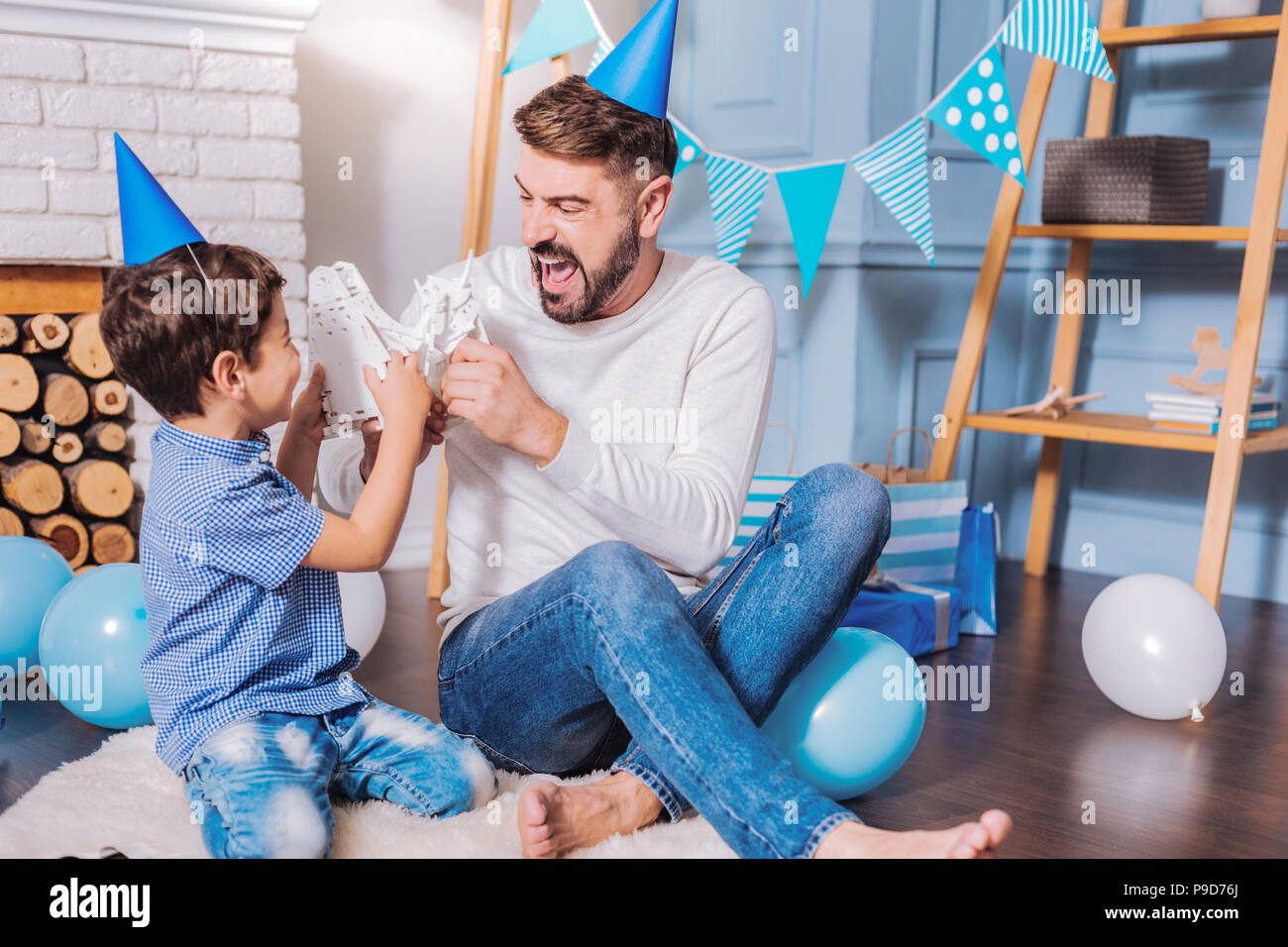 Cheerful bearded male person playing with son Stock Photo