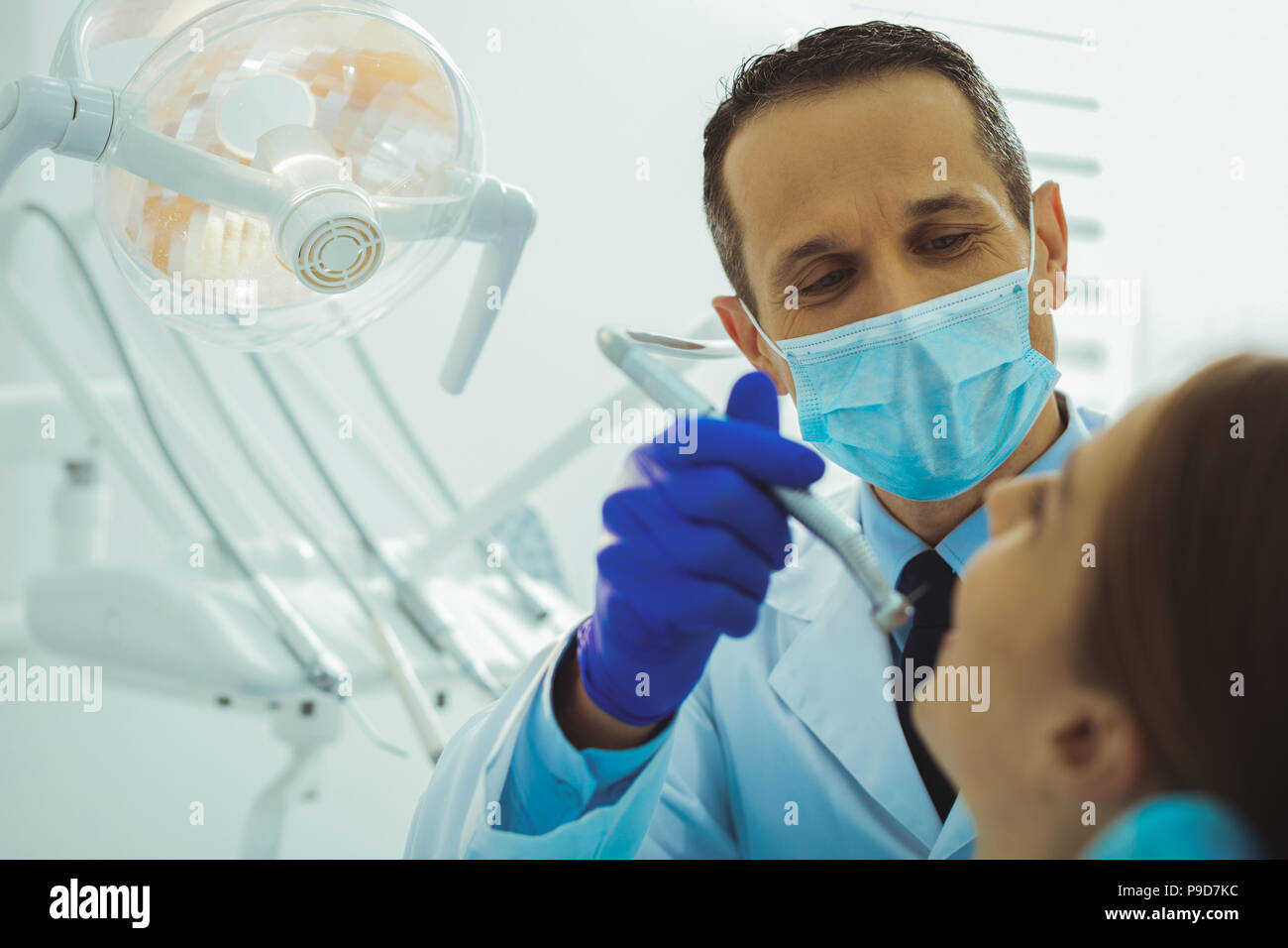 Attentive dentist treating his patient - Stock Image