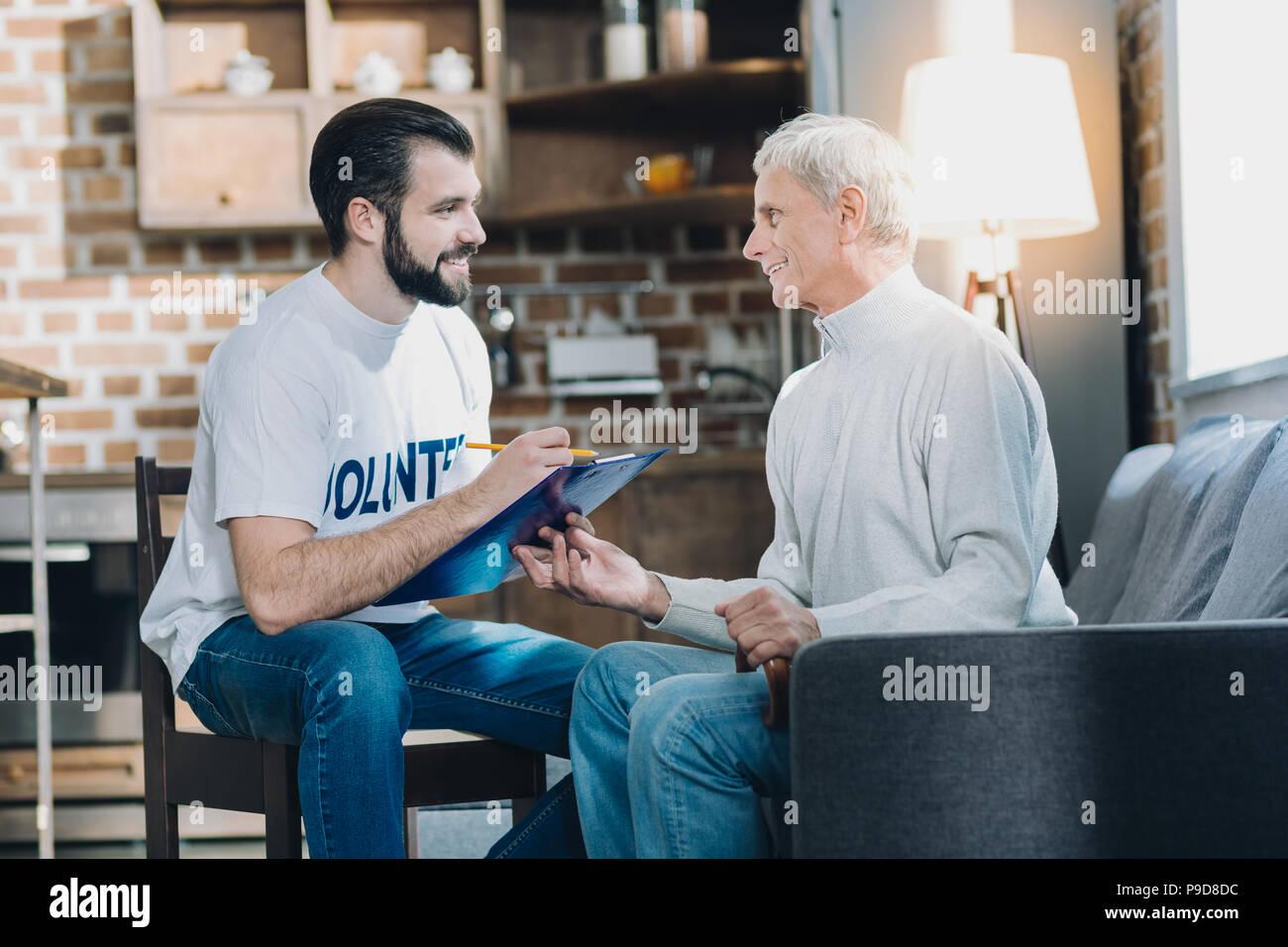 Alert volunteer talking with an old man - Stock Image