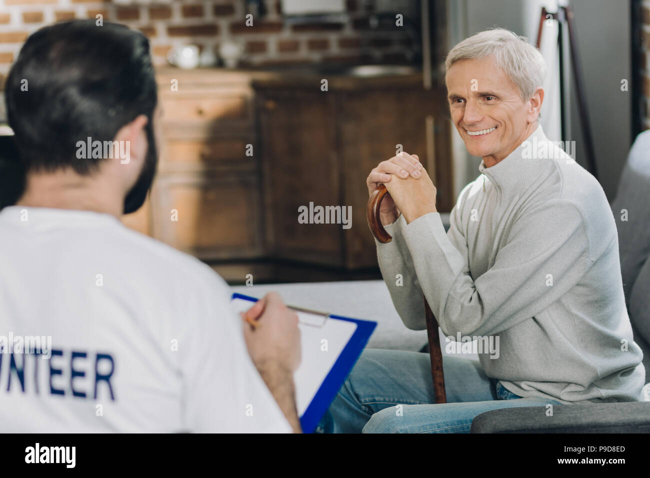 Cheerful old man talking with a volunteer - Stock Image