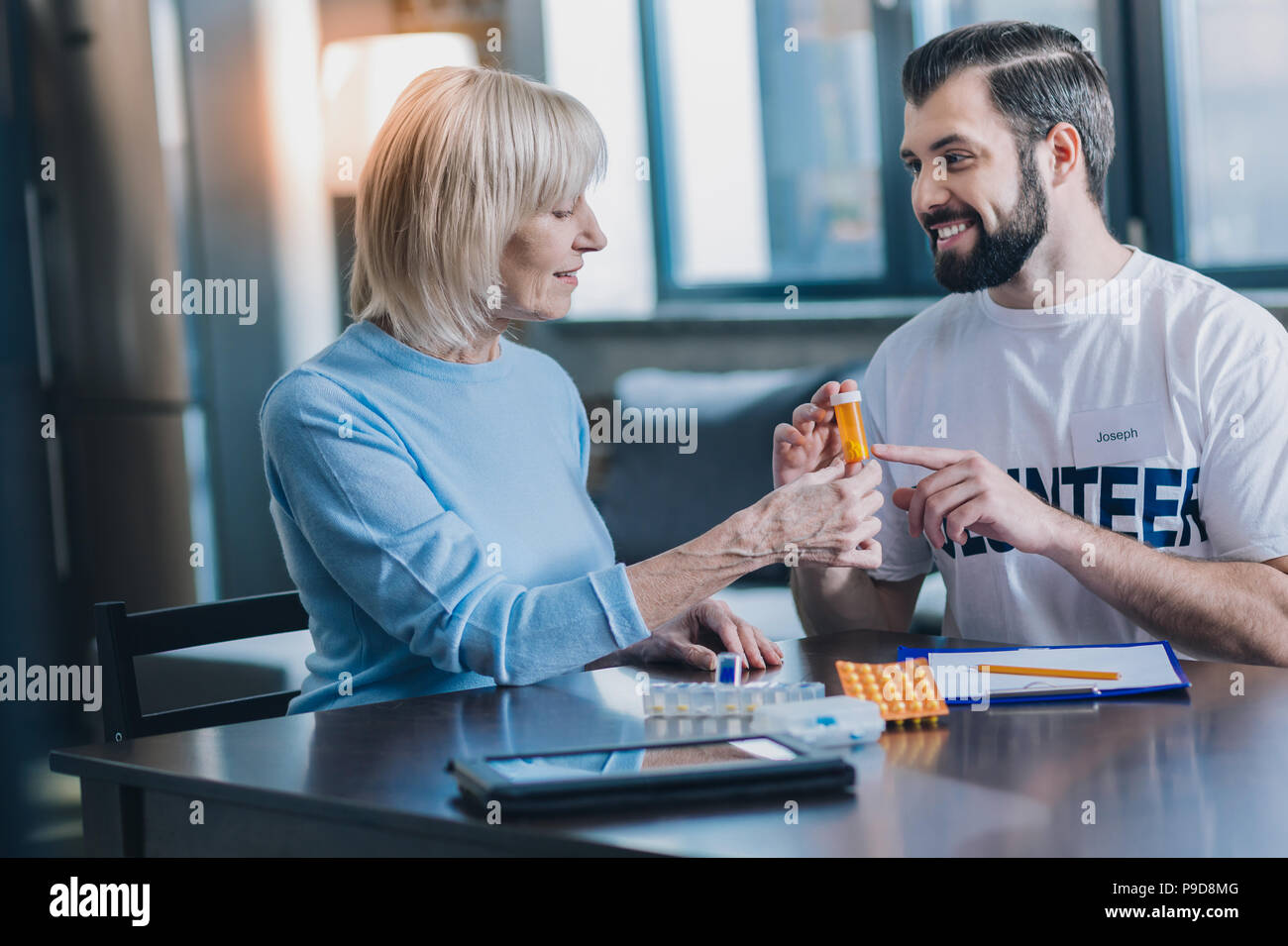 Smiling man advising new pills to a woman - Stock Image