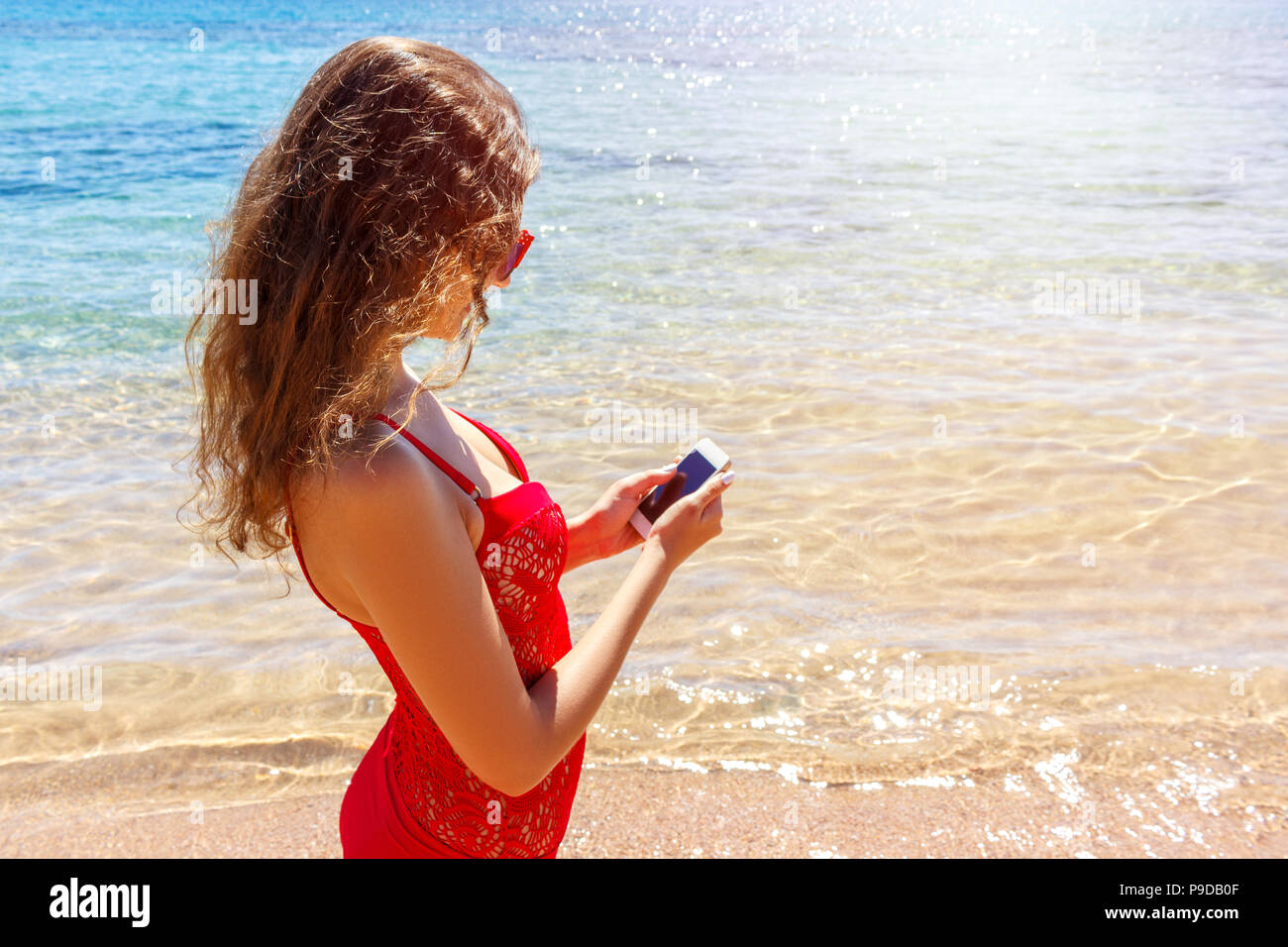 Sunbather girl wearing swimsuit using a smart phone. summer holidays on the beach. - Stock Image