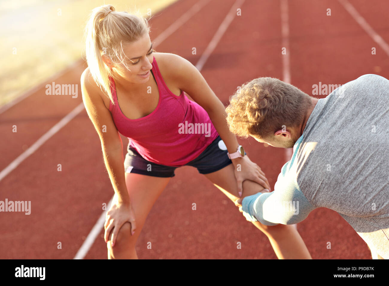Man and woman racing on outdoor track - Stock Image