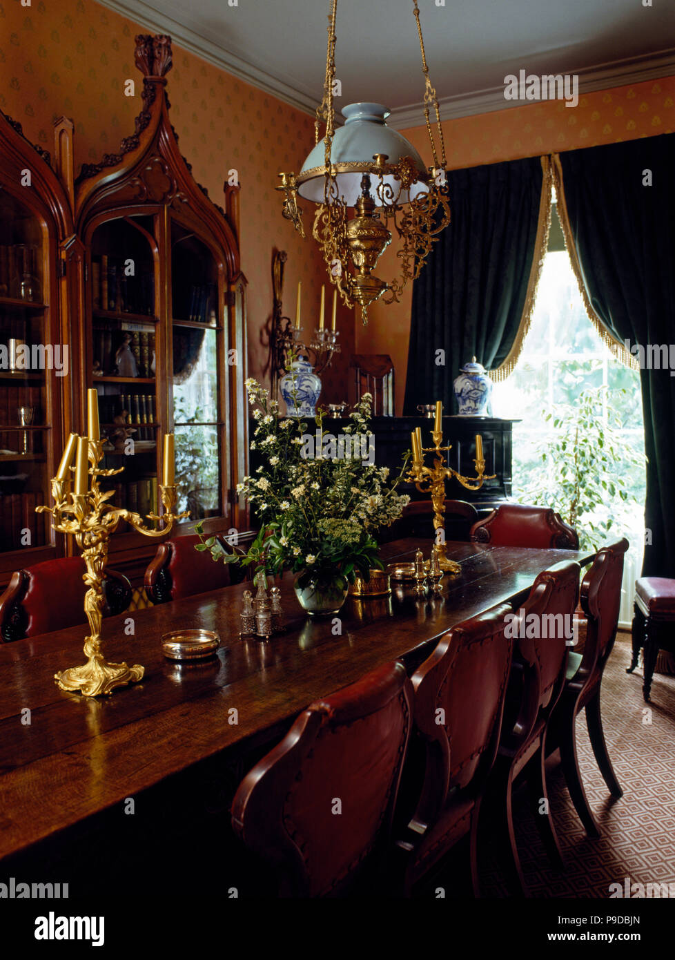 Edwardian style glass and brass light fitting above an antique dining table with gilt candelabra in an old fashioned dining room Stock Photo