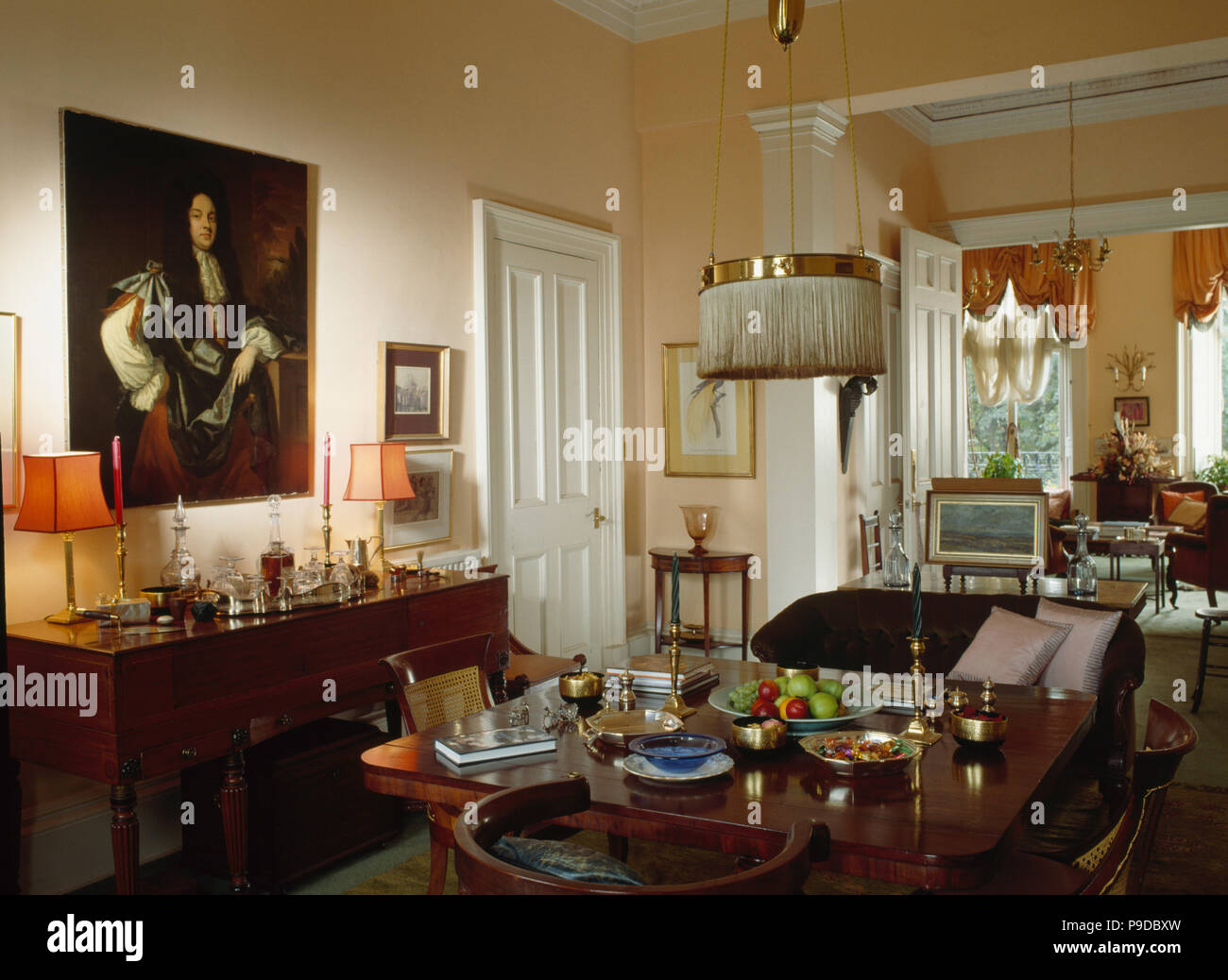 Large oil painting above sideboard in townhouse dining room with antique table and double doors