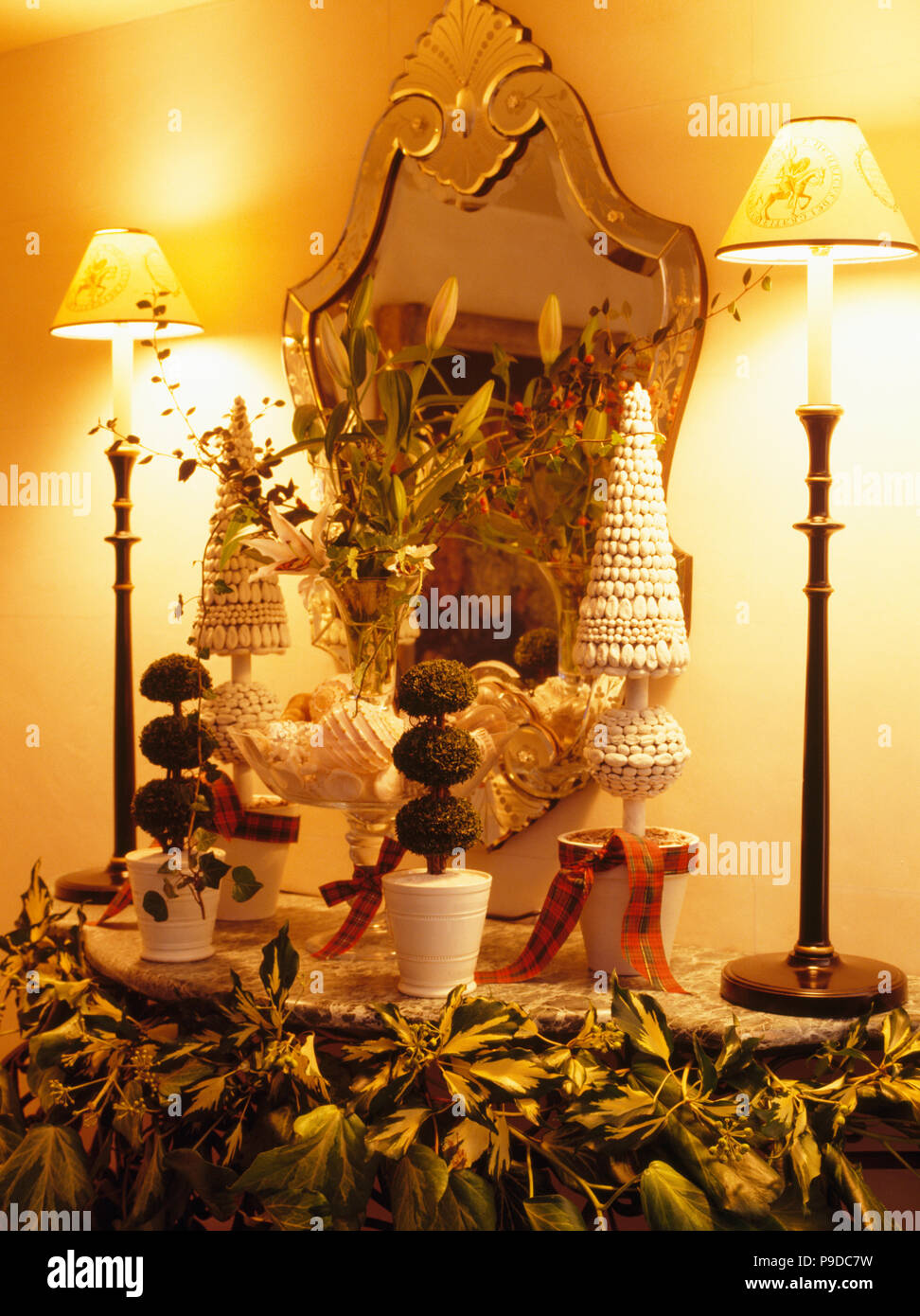 Mirror On Wall Above Shelf With Tall Lighted Lamps And Faux Topiary Trees Stock Photo Alamy