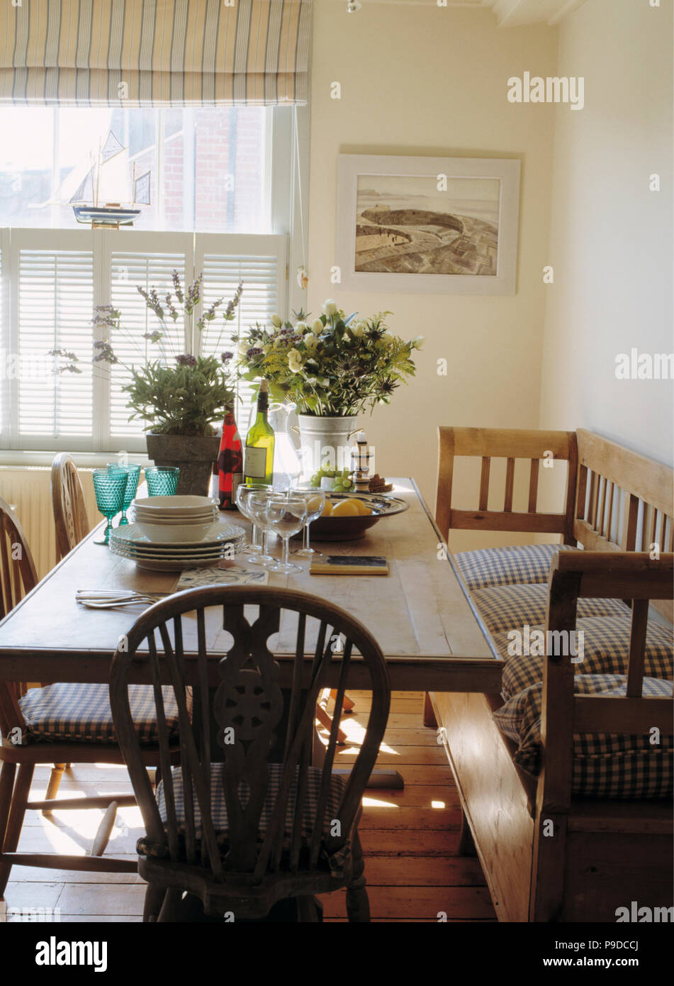 Striped Cushions On Old Wood Settle In Seaside Dining Room With Plates And  Glasses On Wooden Table With Windsor Chairs