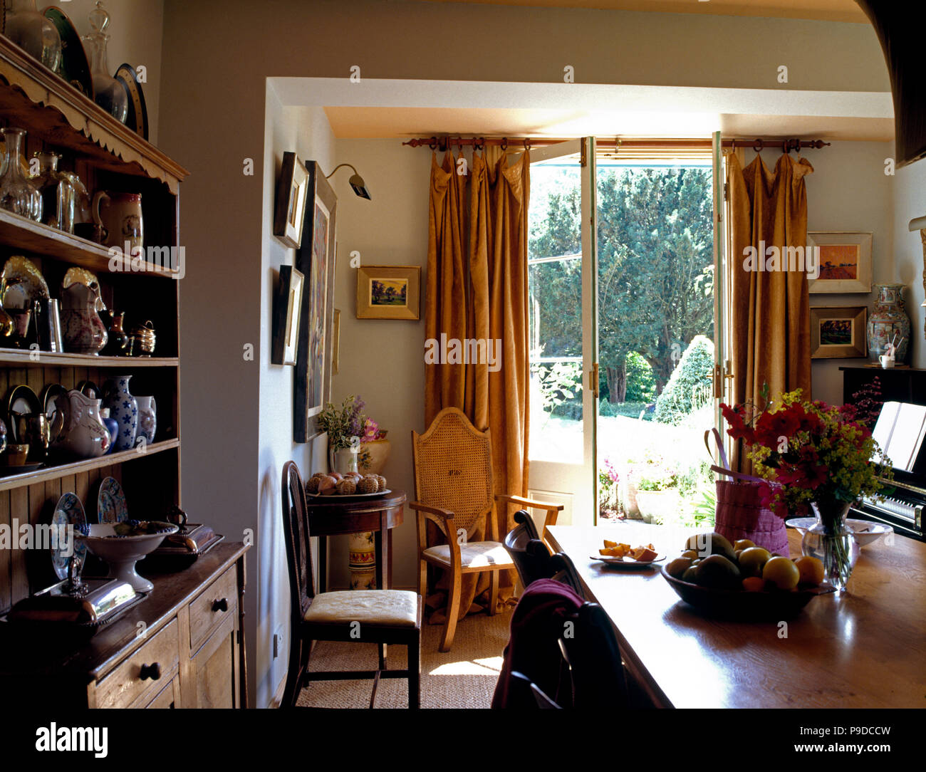 Old Pine Dresser In Small Country Dining Room With Gold Velvet Curtains On French Windows Open To The Garden