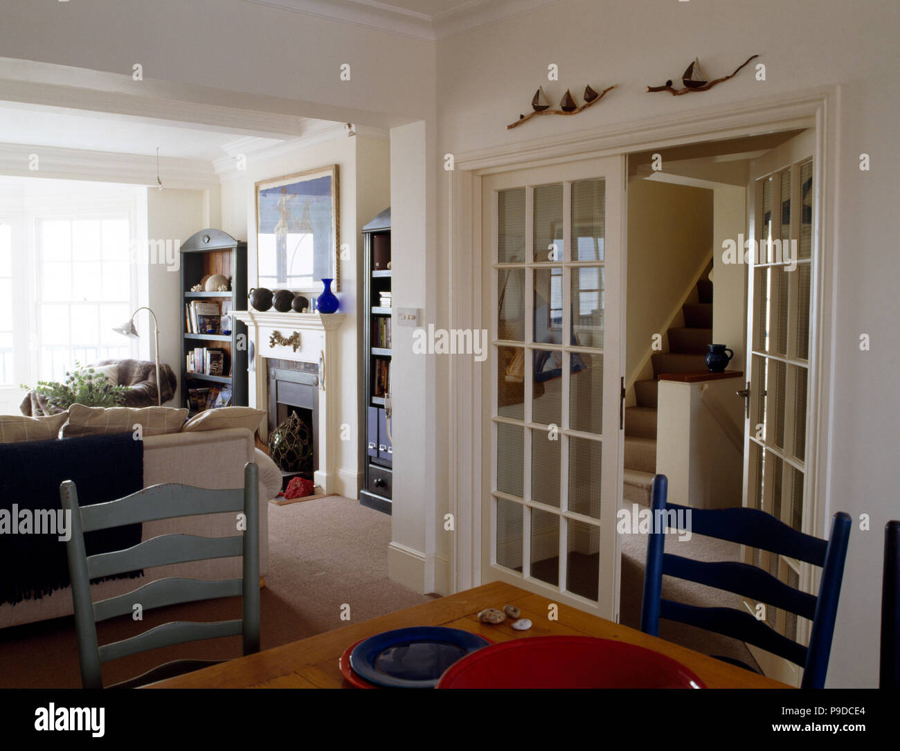 Blue Painted Chairs And Glazed Double Doors In Dining Area Of White Country Living Room