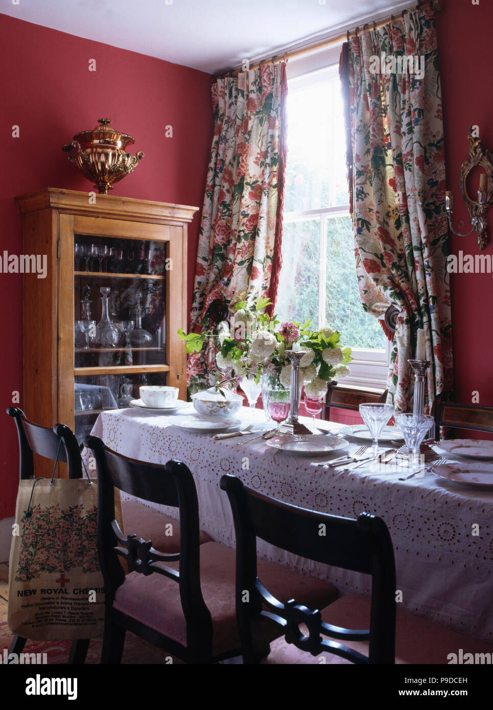 White Linen Cloth On Table Set For Lunch In Madder Red Dining Room With Floral Curtains At The Window Stock Photo Alamy