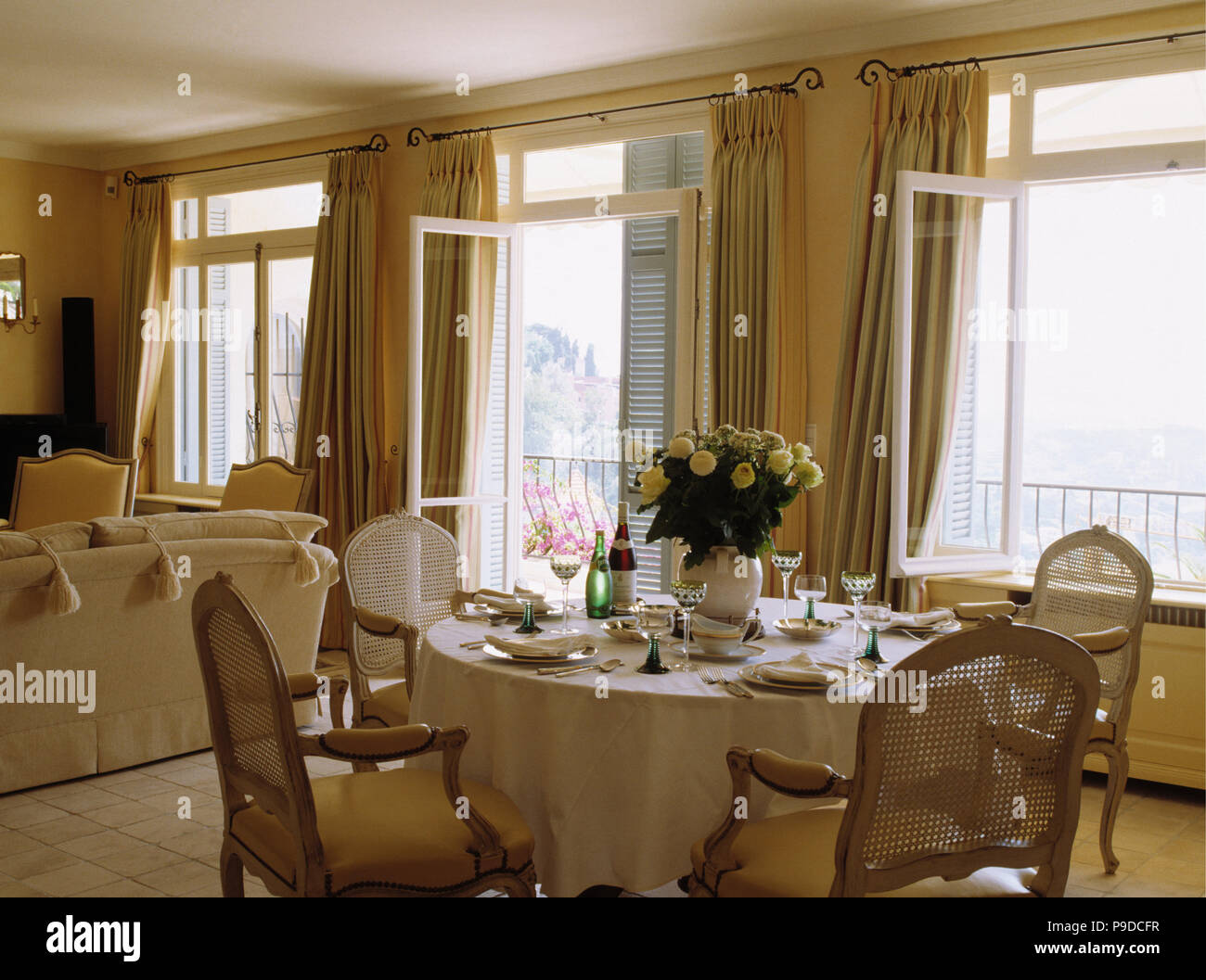 Antique Cane Back Chairs At Table With White Cloth Set For Lunch In Front Of Windows In French Coastal Dining Room Stock Photo Alamy