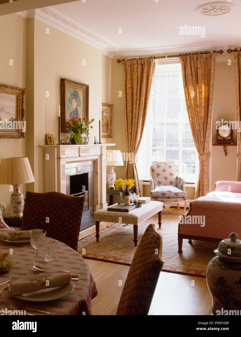 Cream drapes and upholstered stool in a neutral living and ...