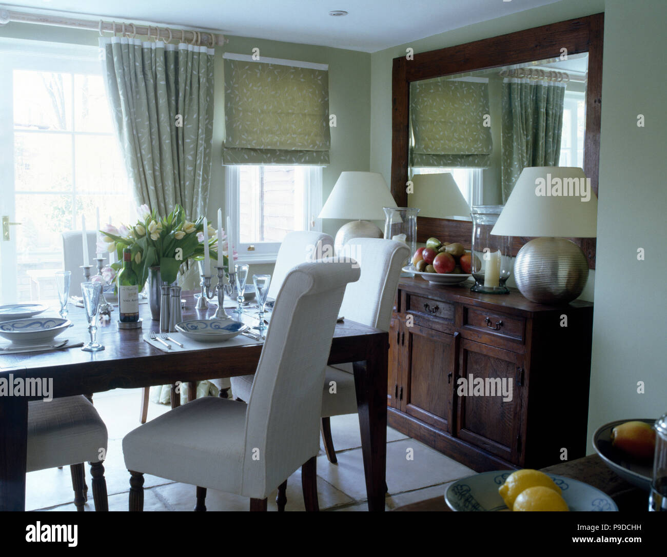 White Upholstered Chairs At Table Set For Lunch In Townhouse Dining Room  With Large Mirror Above Sideboard