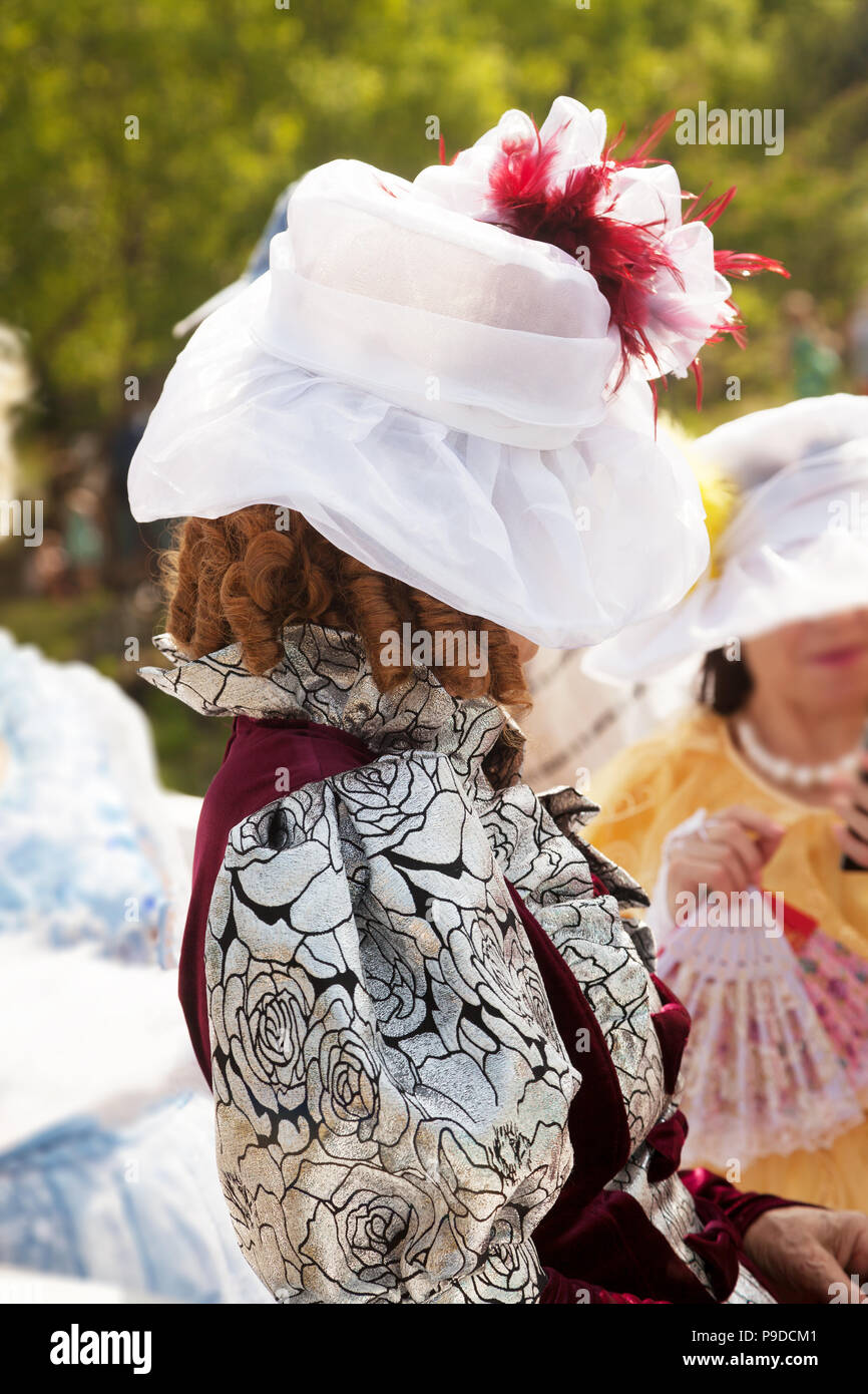 Elderly lady wearing a medieval formal dress and a hat