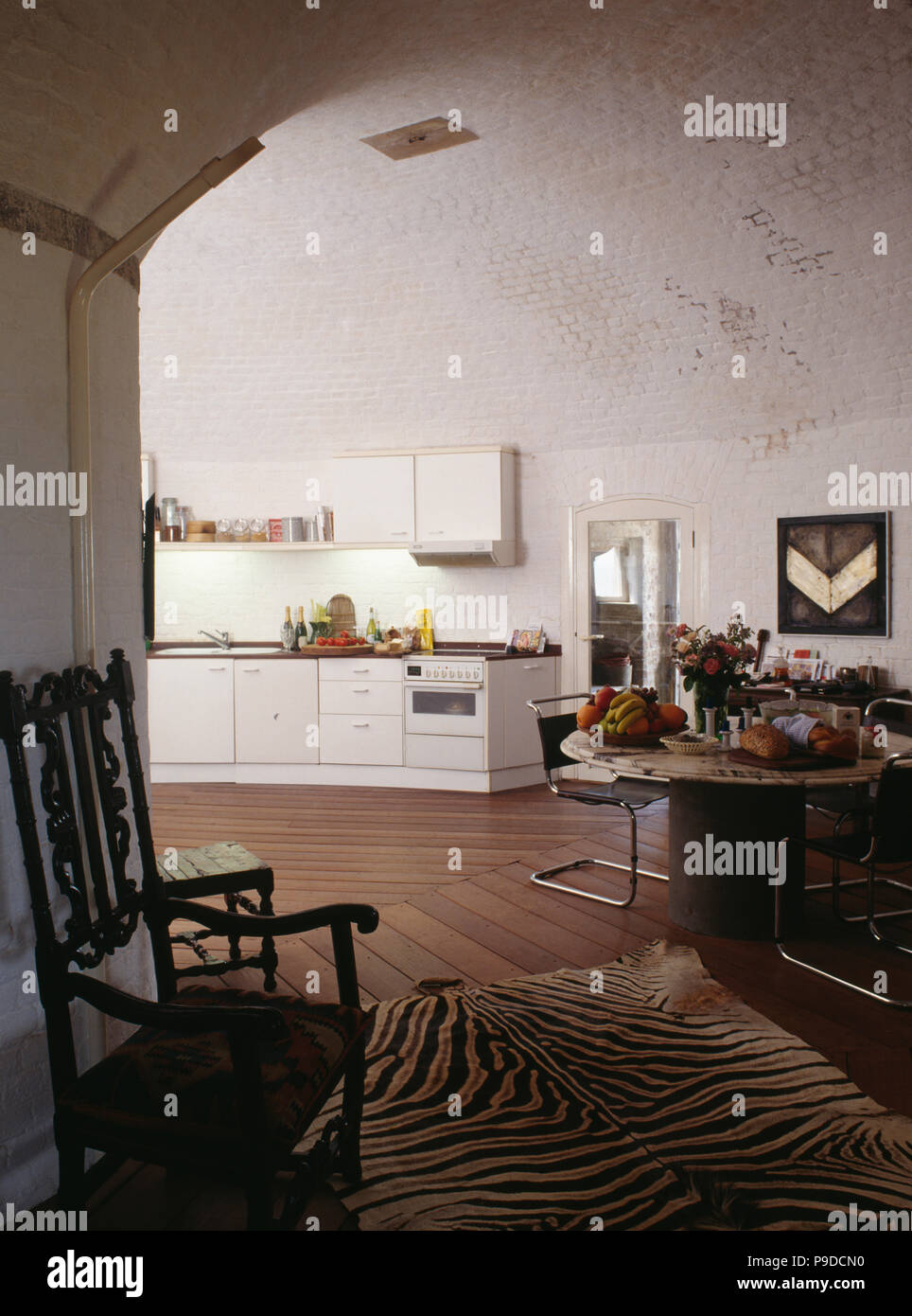 Jacobean chair and old tigerskin rug in dining area of modern kitchen in converted Martello Tower - Stock Image