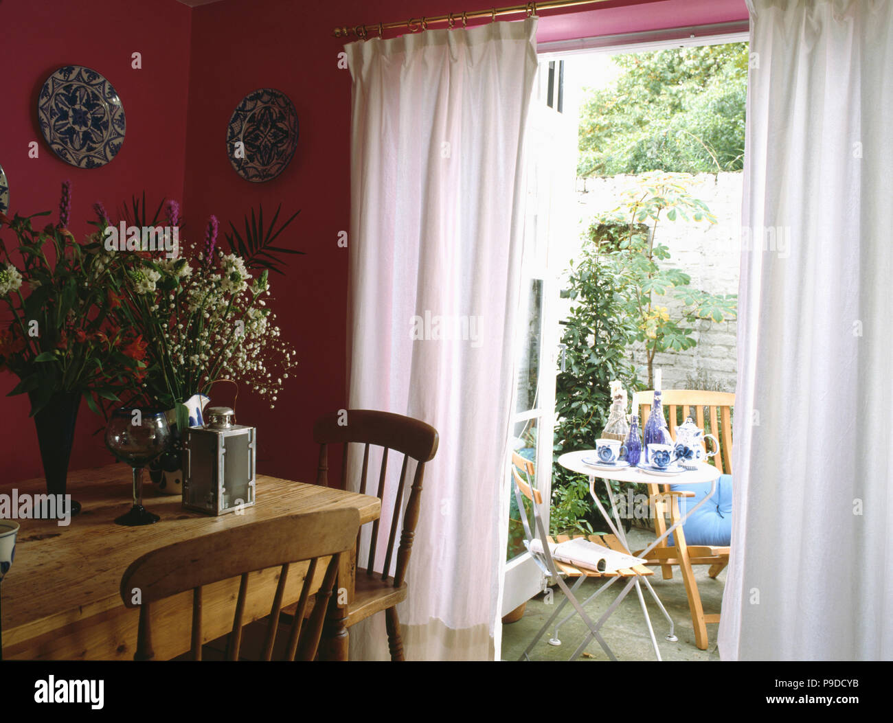 Pine Table And Chairs In Pink Diningroom With White Curtains At French Doors With View Of Patio Garden Stock Photo Alamy