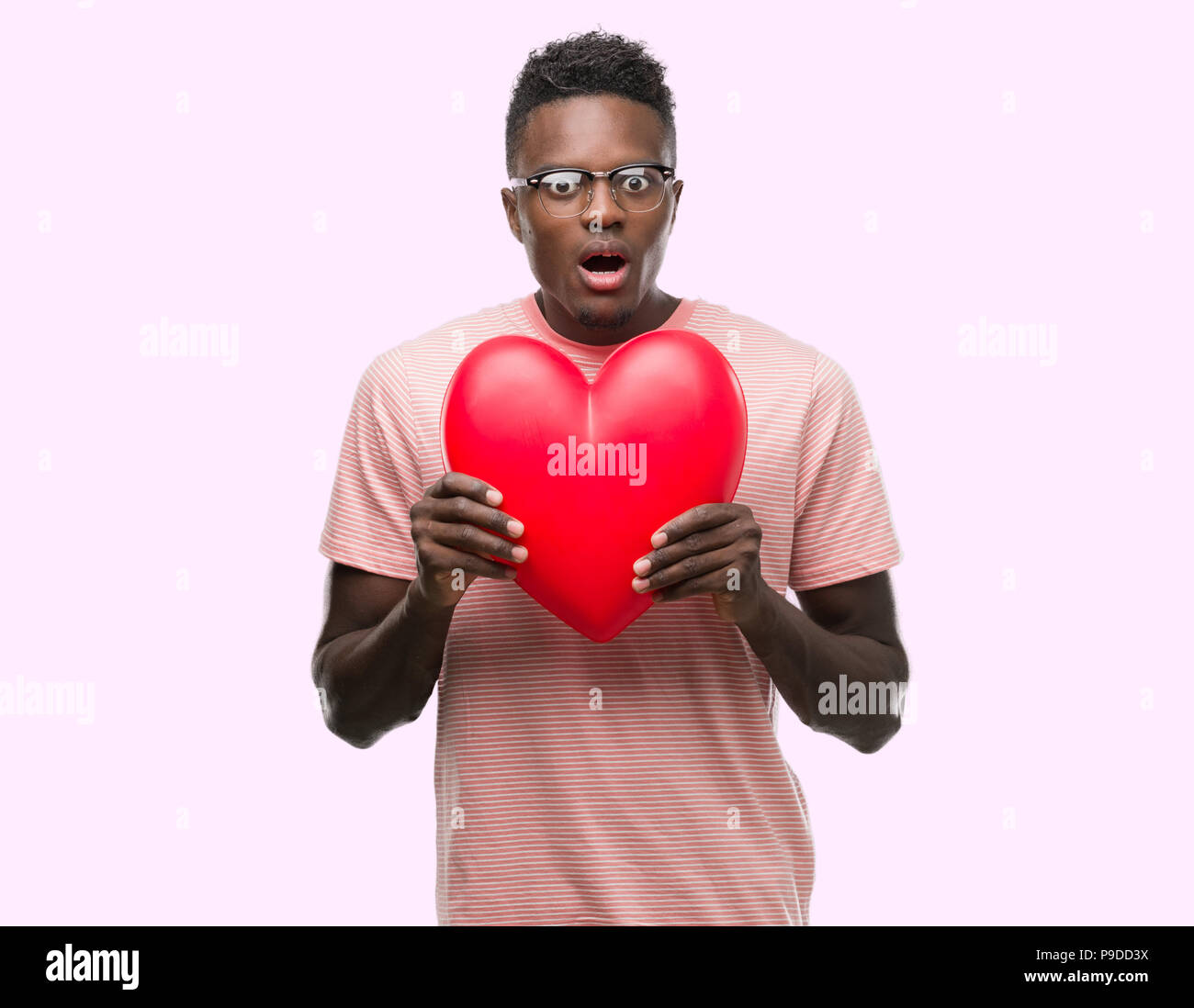 Young african american man holding red heart scared in shock with a surprise face, afraid and excited with fear expression Stock Photo