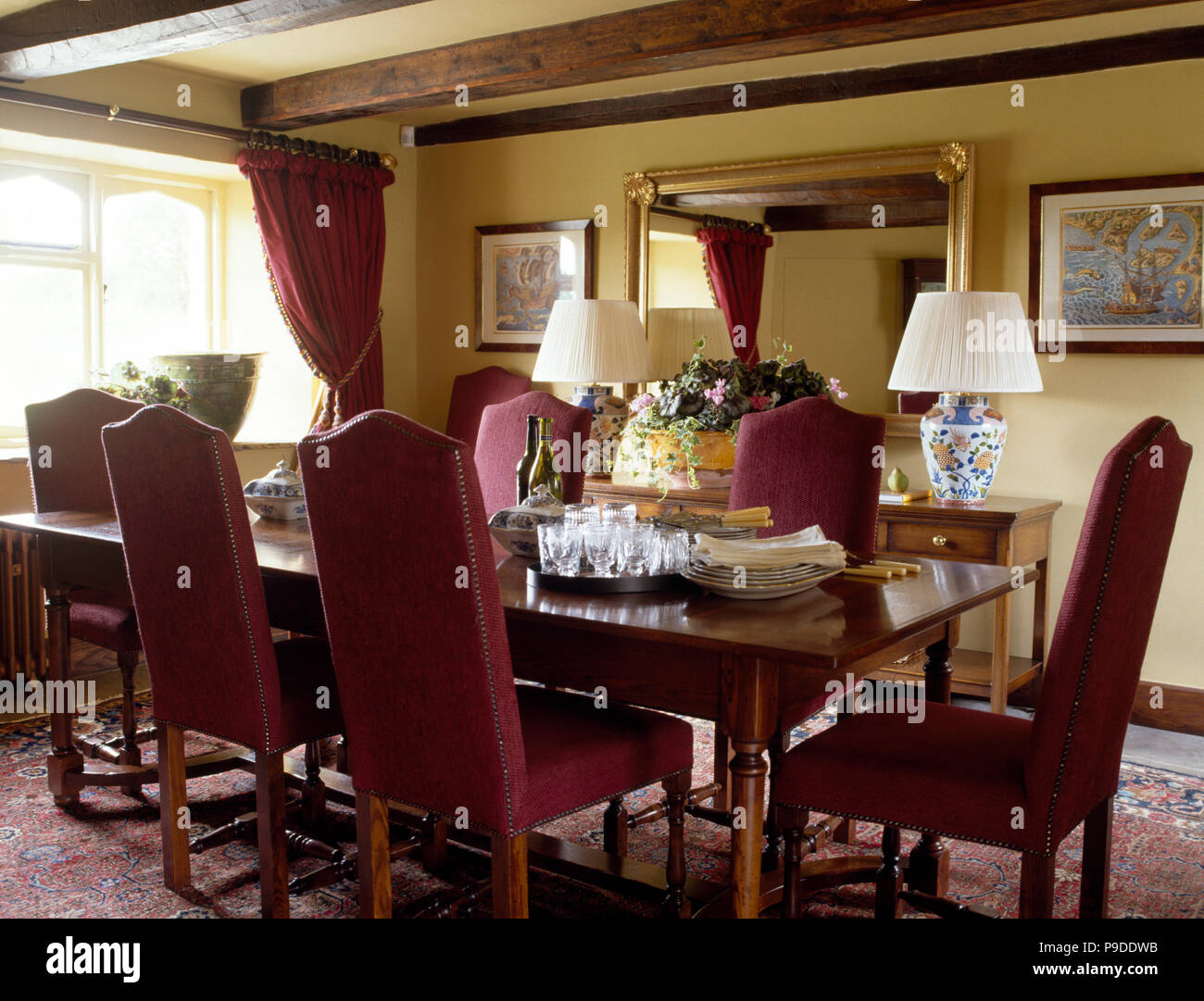 Dark red upholstered chairs at table in pale yellow cottage dining room Stock Photo