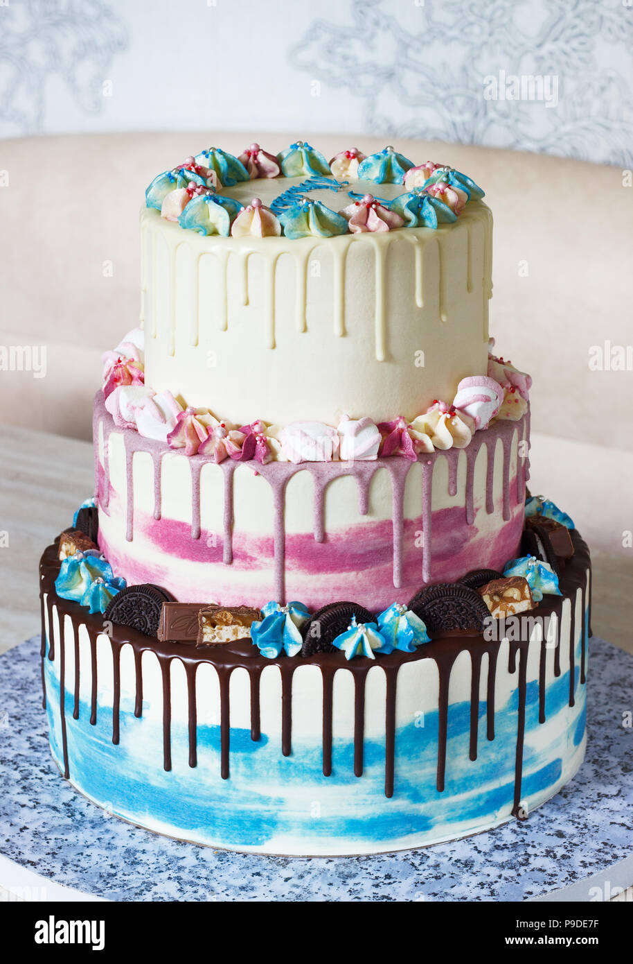Three-tiered colored cake with colored smudges of chocolate on a light background. Picture for a menu or a confectionery catalog with copy space - Stock Image