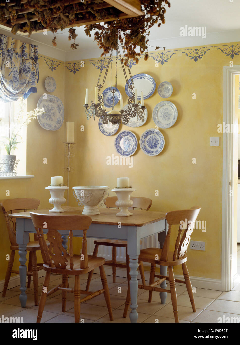 Pine Chairs And Painted Table In A Cottage Dining Room With A Collection Of Vintage Blue White Plates On The Wall Stock Photo Alamy