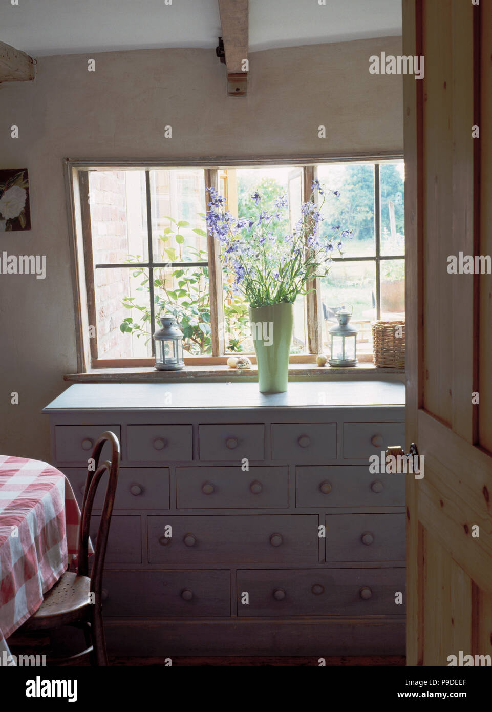 Door Open To Vase Of Flowers On White Painted Chest Of Drawers Below Window  In White Cottage Dining Room
