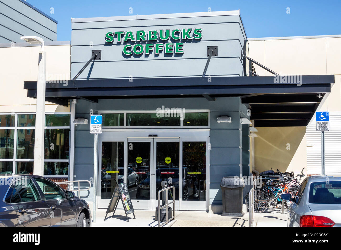 Florida Gainesville Starbucks Coffee coffeehouse front entrance exterior disabled parking space - Stock Image