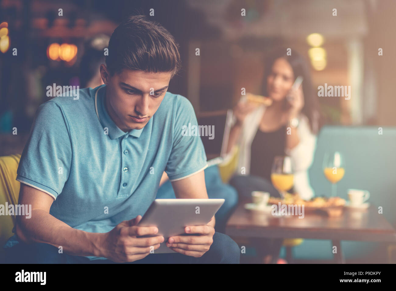 Young male using digital tablet in modern startup office - Stock Image