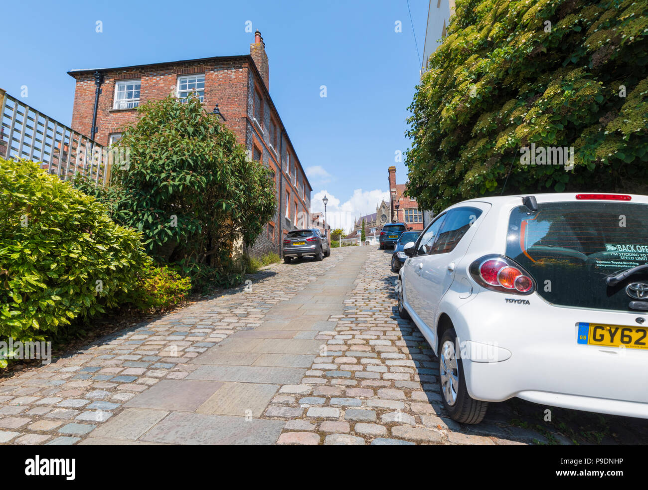 Cars parked on Kings Arms Hill, a historic cobbled road on a steep hill in the historic market town on Arundel, West Sussex, England, UK. - Stock Image