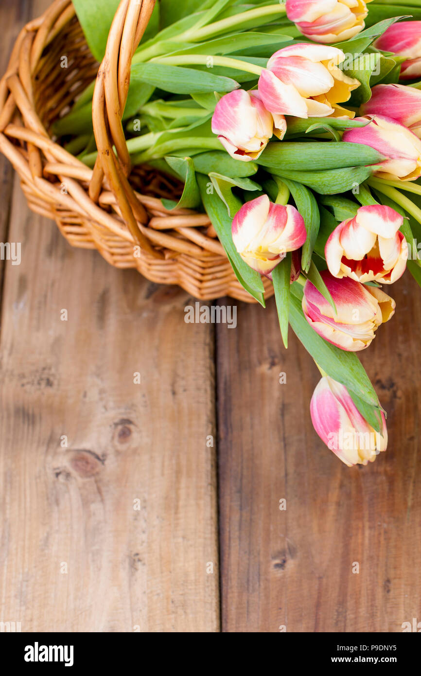 A bouquet of tulips with yellow and red for a gift. On a brown wooden background. Free method for text. - Stock Image