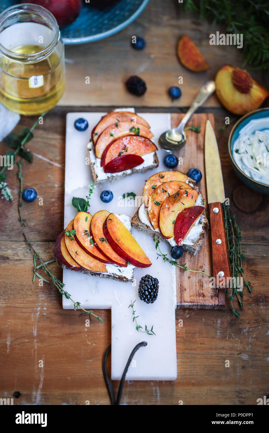 Fresh herbs goat cheese mousse and peaches crostini. - Stock Image