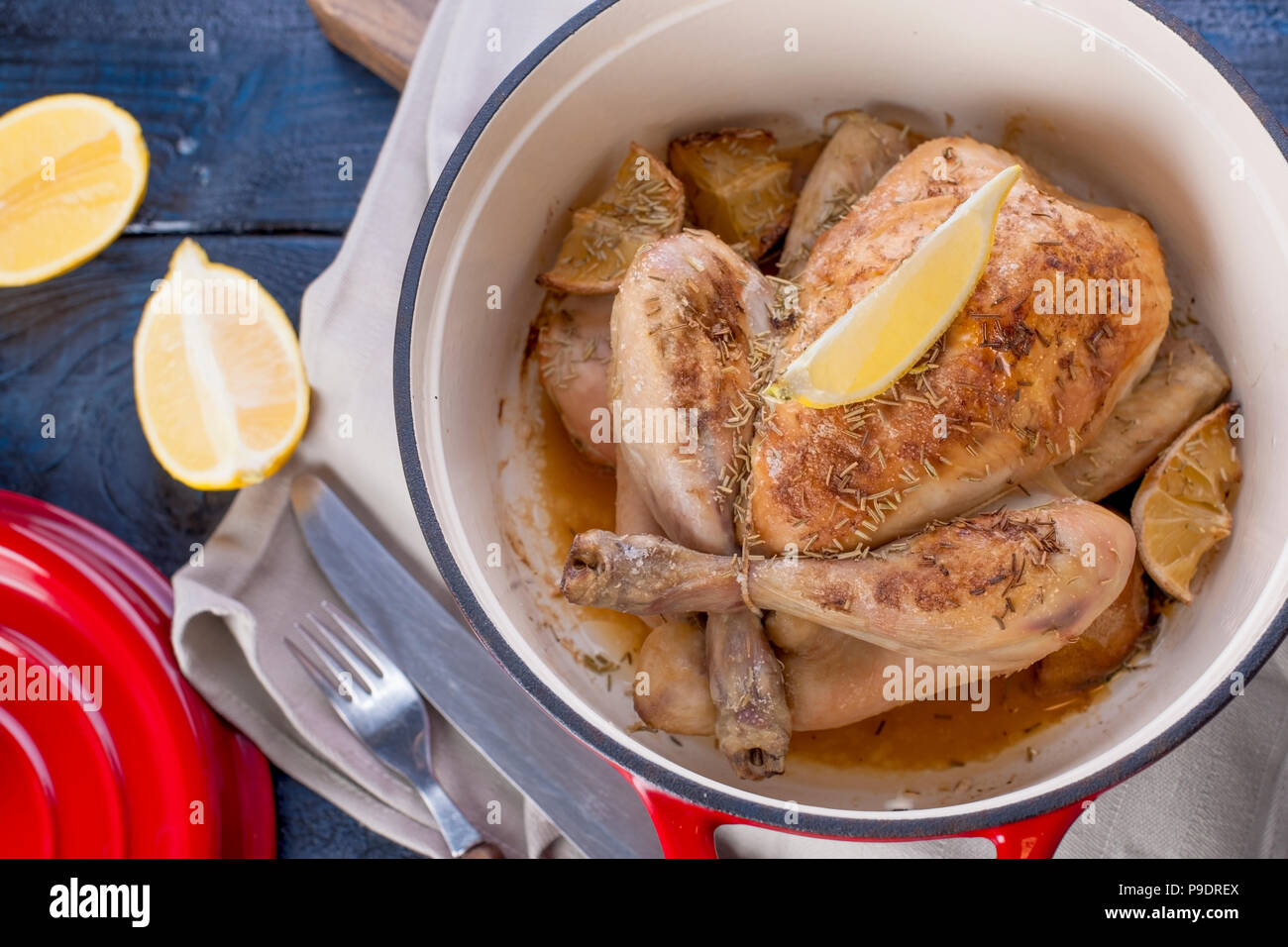The whole chicken baked with lemon and rosemary in a red cast iron. Blue wooden background and gray towel. Knife and fork. Free space for text. - Stock Image