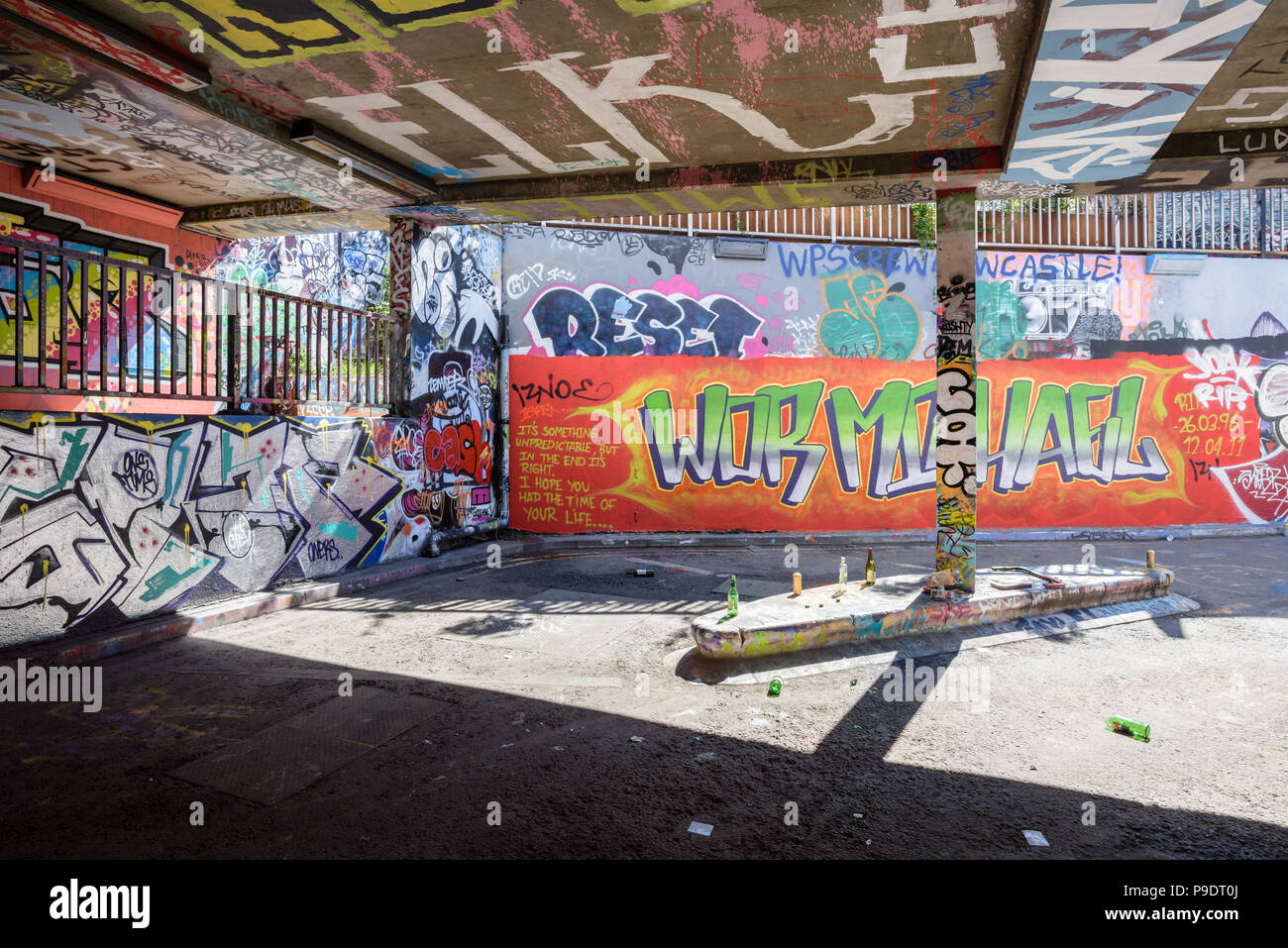 Empty bottles and cans of alcohol left in Banksy Tunnel in Leake Street in Waterloo, London, against a backdrop of graffiti on walls Stock Photo