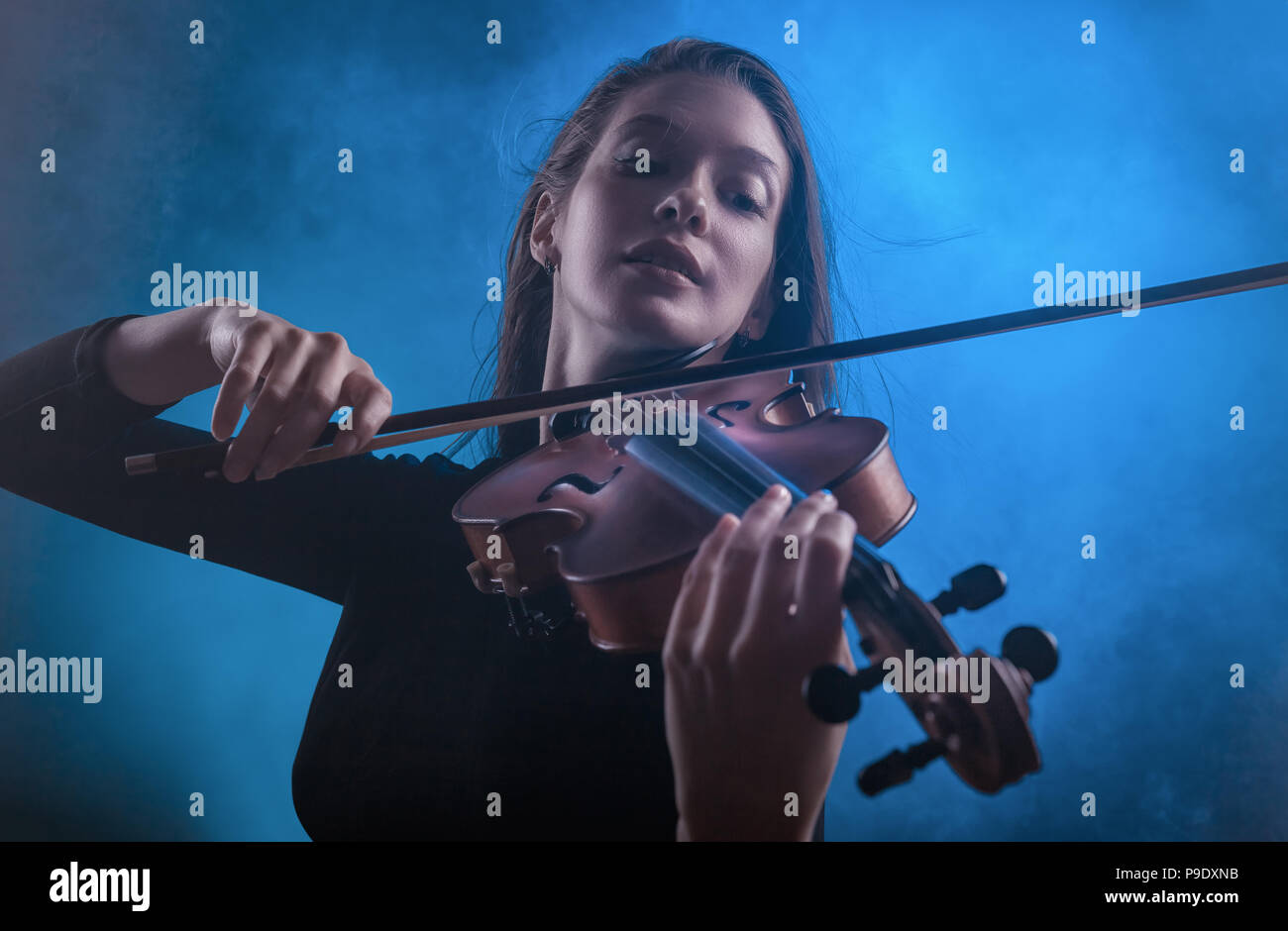 Beautiful young woman playing the violin against a dark background - Stock Image