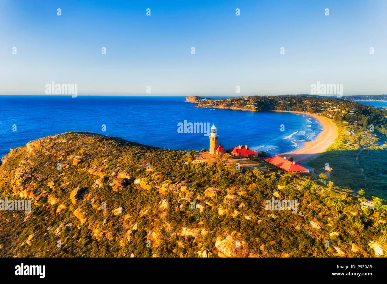 Barrenjoye head lighthouse high above Northern beaches coast of Sydney rising above Palm beach on a bright calm morning lit by warm sun light. - Stock Image