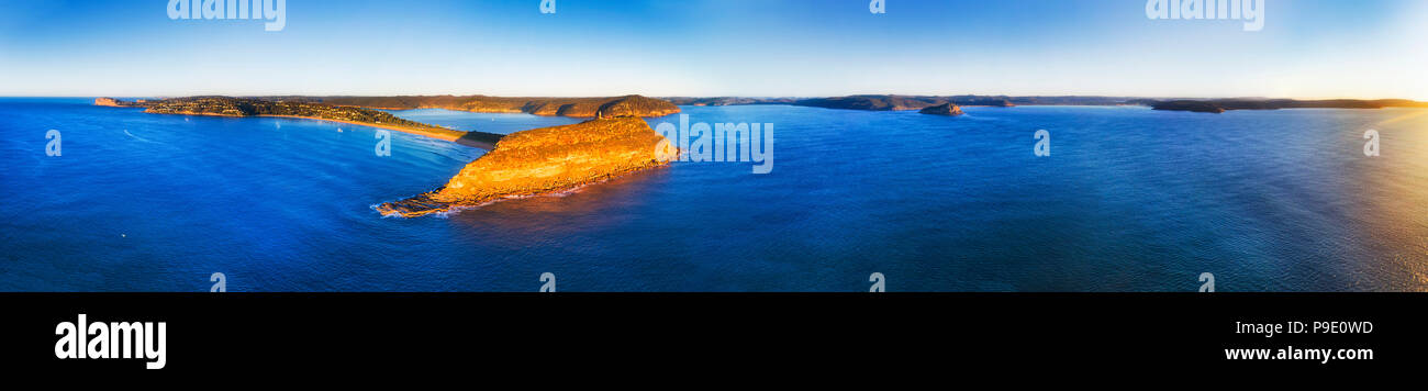 Palm beach and Barrenjoye head on Sydney Northern beaches coast at the entrance of Hawkesbury river at sunrise in ultra wide seascape panorama. - Stock Image