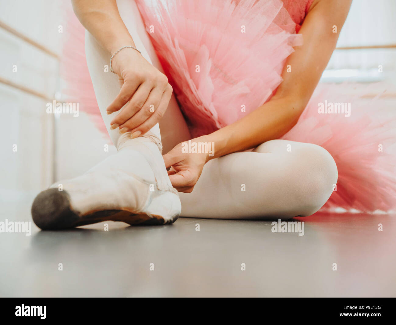 Young ballerina in pink tutu costume wraps white silk ribbons of soft top ballet shoes pointe and ties them up. Woman preparing for dance training lessons in gym. - Stock Image