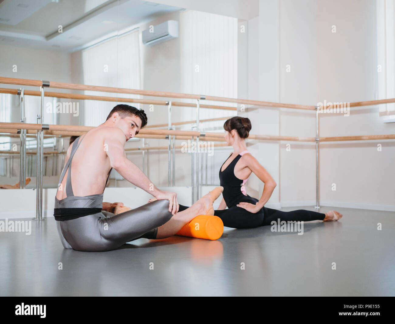 Preparation of body before performance in ballet studio. Male dancer and ballerina warming up near barre on rehearsal. - Stock Image