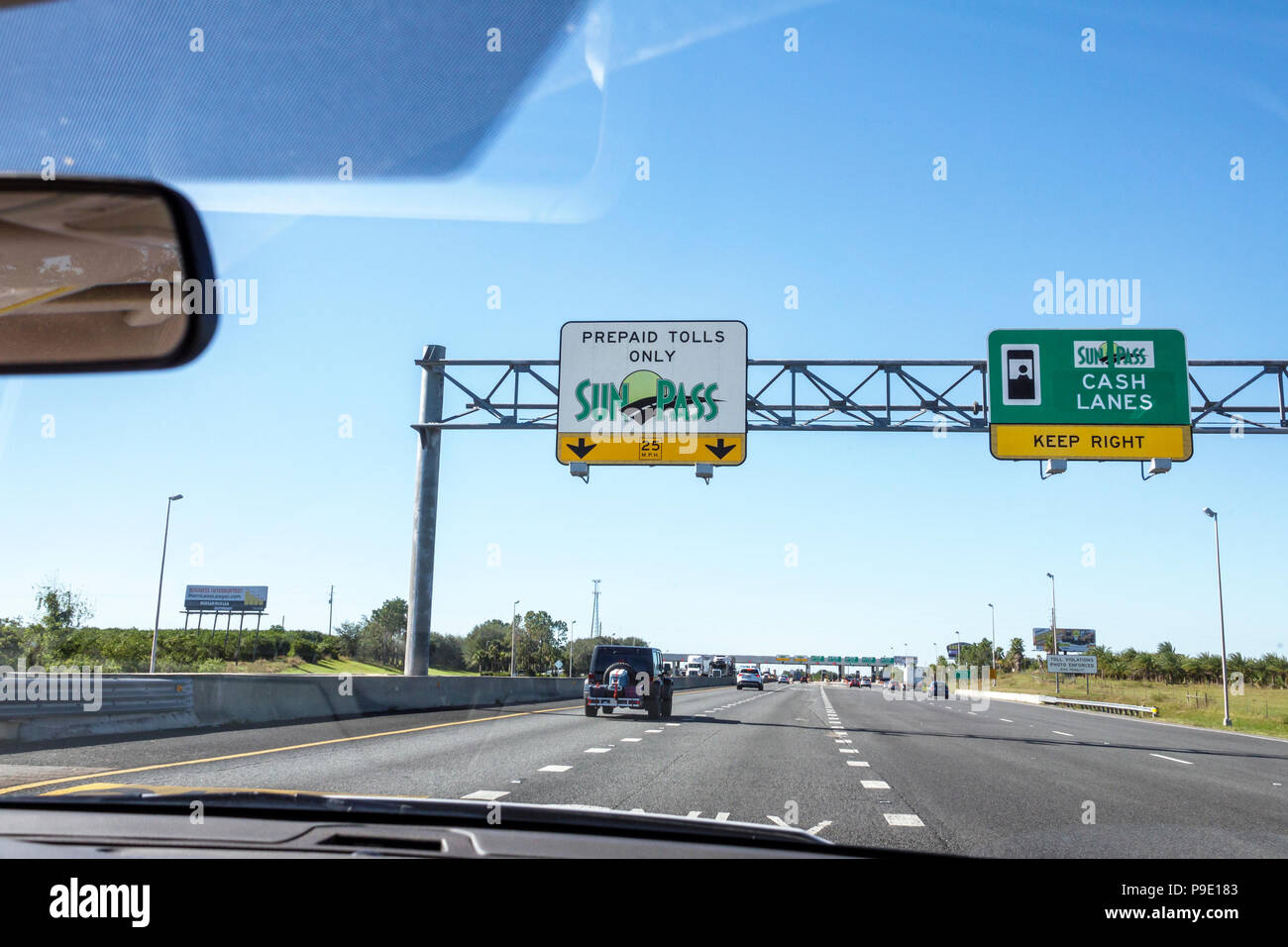 Florida Winter Park Florida Turnpike toll road plaza SunPass prepaid electronic toll tolls collection system highway traffic driving window windshield - Stock Image