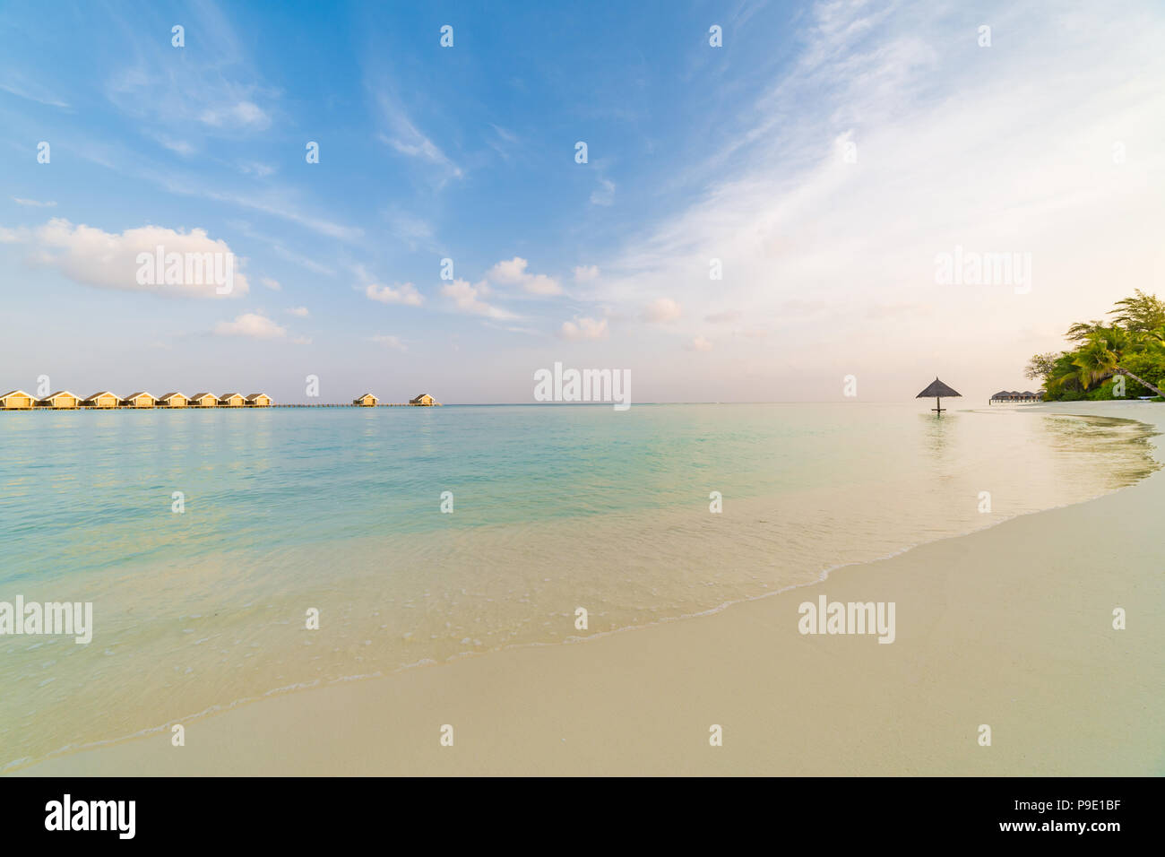Amazing Maldives scenery, water villas and beach umbrella with palm trees. Tranquil sunset landscape in tropical beach. Luxury vacation destination Stock Photo