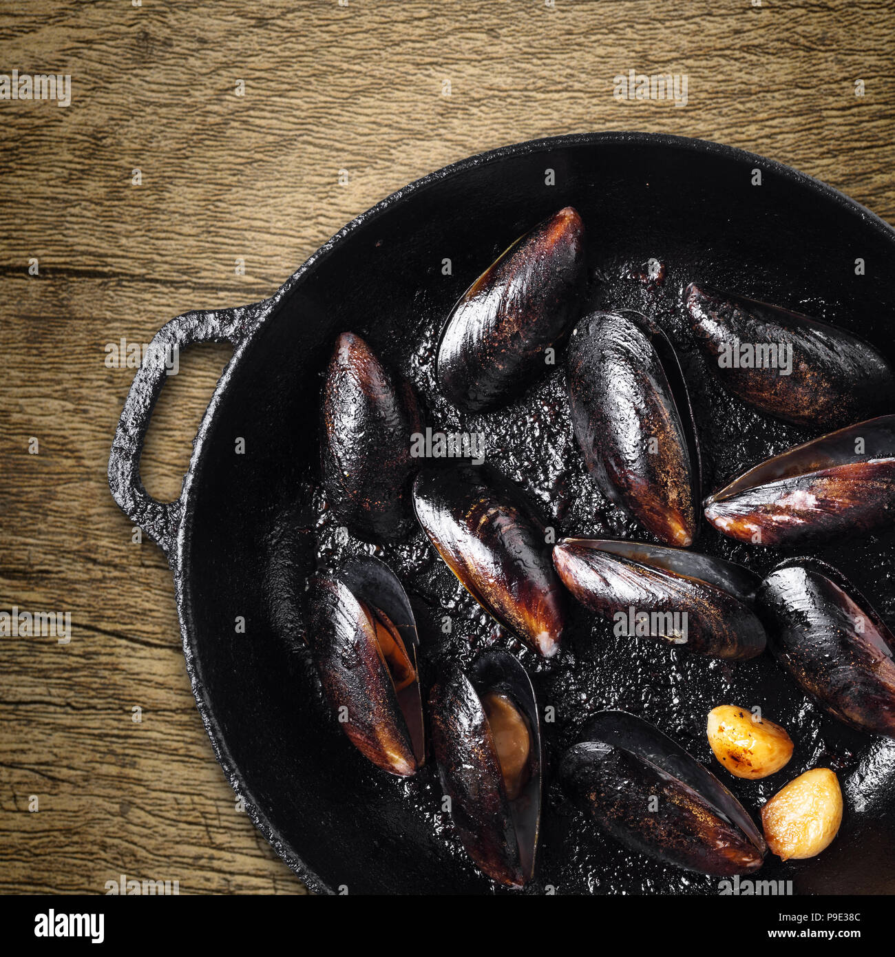 frying pan with cooked mussels on wooden background - Stock Image