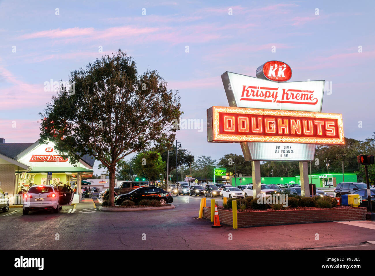 Florida Gainesville Krispy Kreme Doughnuts neon sign night nightlife coffeehouse chain twilight dusk parking lot cars - Stock Image