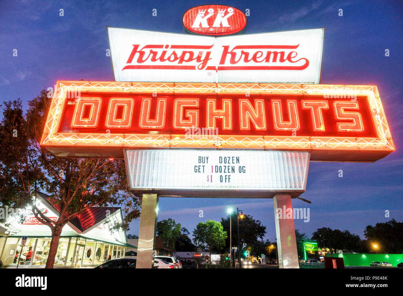 Florida Gainesville Krispy Kreme Doughnuts neon sign night coffeehouse chain twilight dusk parking lot cars sale promotion - Stock Image