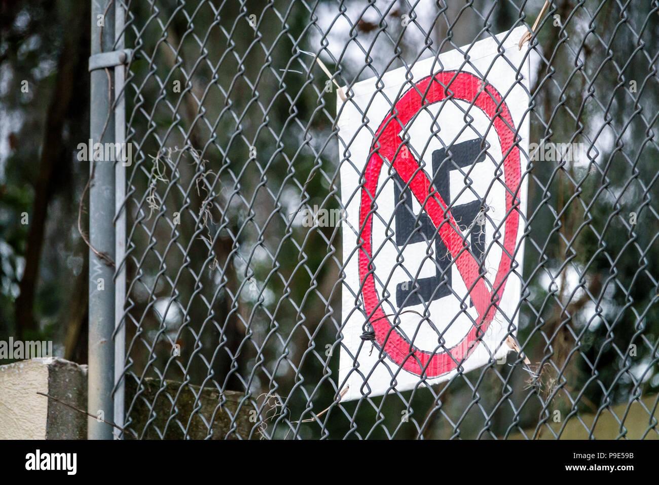 Florida Gainesville anti-Nazi sign Hakenkreuz swastika hate symbol chain-link fence - Stock Image