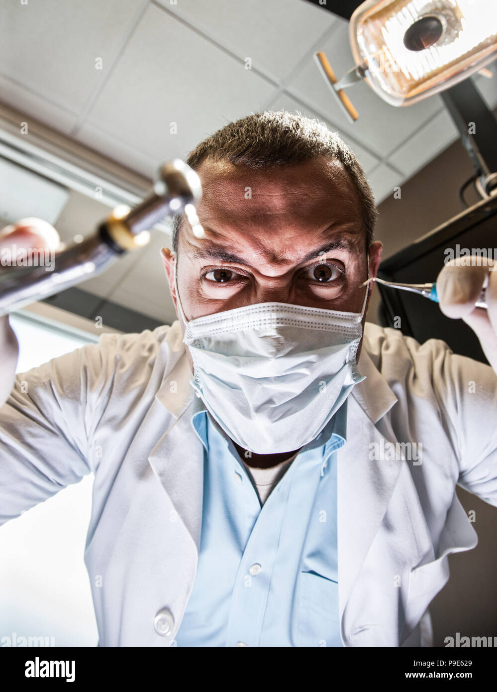 A dramatic view looking up from a patient's perspective of a scary looking dentist holding tools. - Stock Image