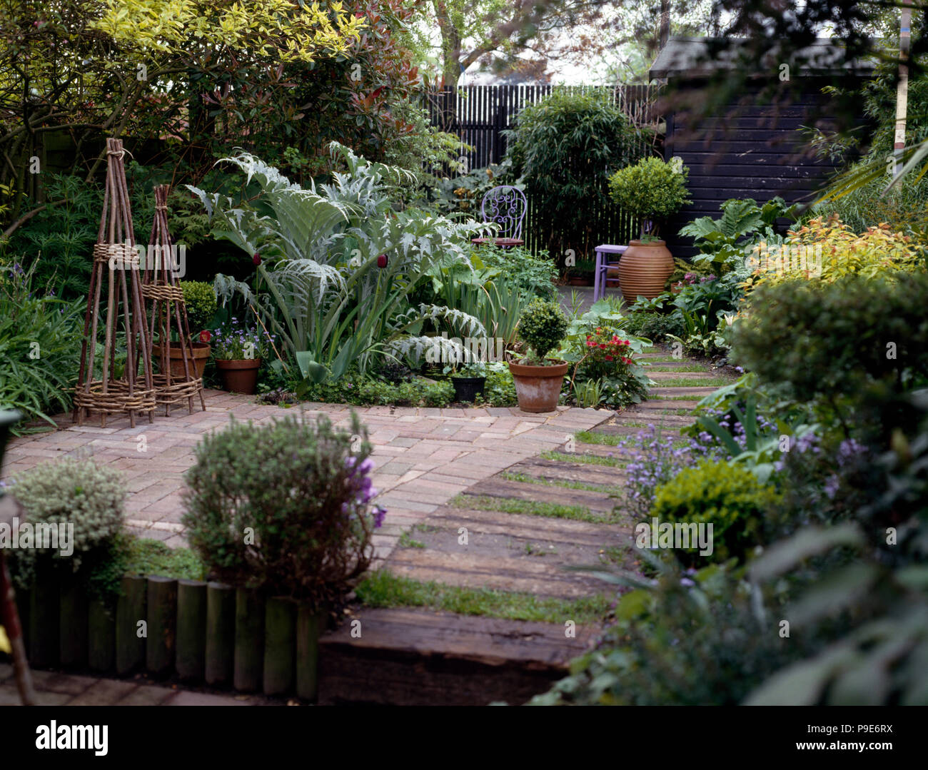 Willow Obelisks On Small Terrace In Townhouse Garden With Lush
