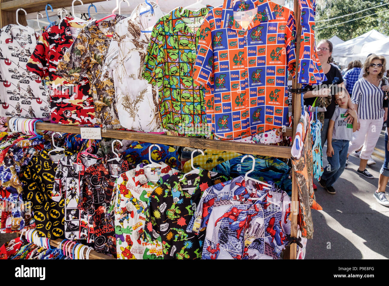 Florida Micanopy Fall Harvest Festival annual small town community event booths stalls vendors buying selling display sale men's theme shirts UF logo - Stock Image