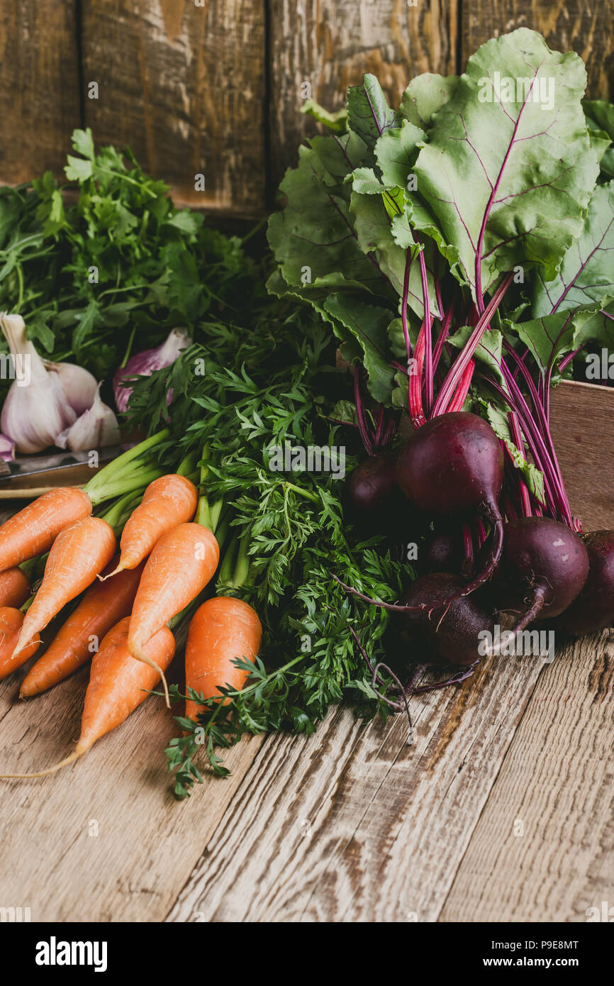 Fresh organic autumnal vegetables. Vegetarian  food cooking ingredients on rustic wooden table - Stock Image