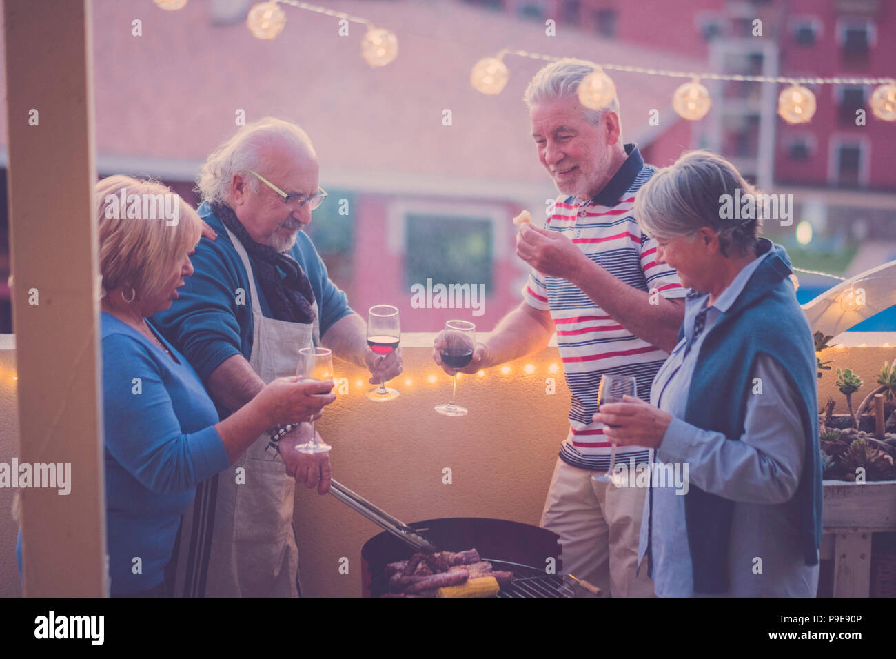 senior adult people group in leisure activity doing barbeque bbq on the rooftop terrace at home with mountain view. meal and wine for two men and two  - Stock Image