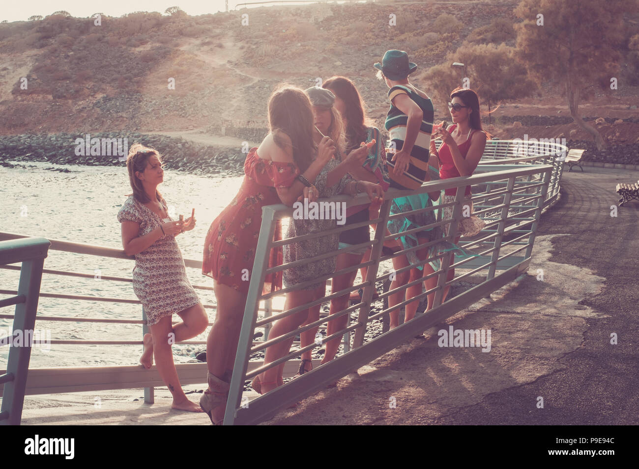 group of seven nice and beautiful caucasian girls young women have fun and laugh and smiles outdoor near the ocean during the sunset. backlight paople - Stock Image